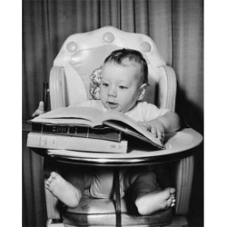 Posterazzi SAL2559707 Baby Sitting in a High Chair & Looking at a Book Poster Print - 18 x 24 in.