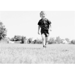 Posterazzi SAL255424655 Little Boy Walking on Field Poster Print - 18 x 24 in.