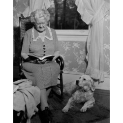 Posterazzi SAL255424317 Senior Woman Sitting in Armchair Reading Book with Dog Beside Poster Print - 18 x 24 in.
