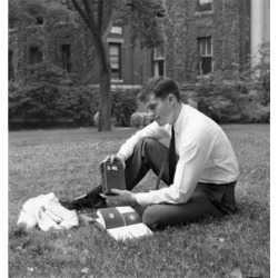 Posterazzi SAL255420785 Portrait of Male Student Reading Book & Listening to Radio Outside University Building Poster Print - 18 x 24 in.