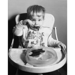 Posterazzi SAL2559717 Baby Sitting in a High Chair & Eating Baby Food Poster Print - 18 x 24 in.