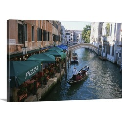 Large Gallery-Wrapped Canvas Wall Art Print 24 x 16 entitled A gondolier passes a restaurant on a canal in Venice, Italy