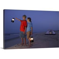 Large Solid-Faced Canvas Print Wall Art Print 30 x 20 entitled A boy and a girl stand with lanterns on the beach with a te...
