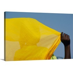 Large Gallery-Wrapped Canvas Wall Art Print 30 x 20 entitled A person with their back to the camera holds up a yellow piec...