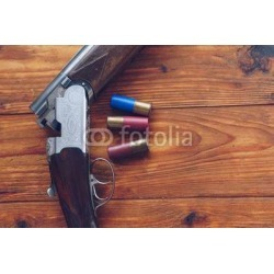 Shotgun And Hunting Cartridges On Wooden title=
